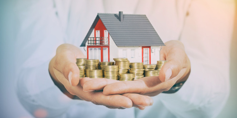 Mortgage concepts. House and money coins on hand.